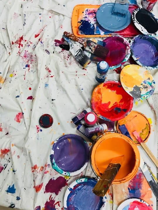 Diverse Farbkübel mit unterschiedlichen Farben auf Malerpapier