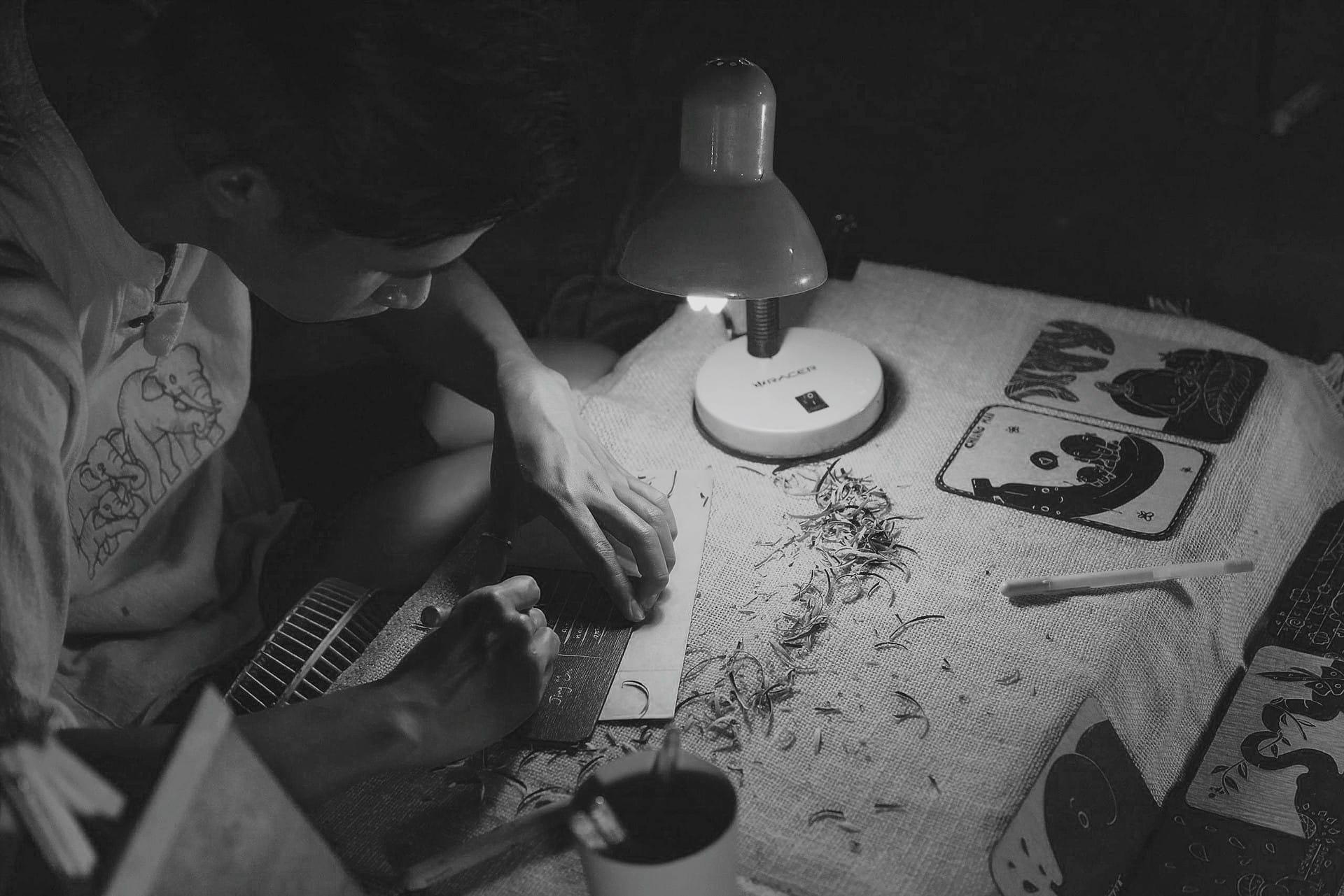 Mann beim Gravieren einer Tafel auf einem Holztisch