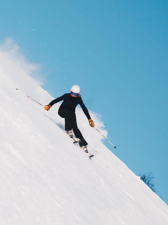 Schifahrerin in einer Kurve auf einer steilen Piste
