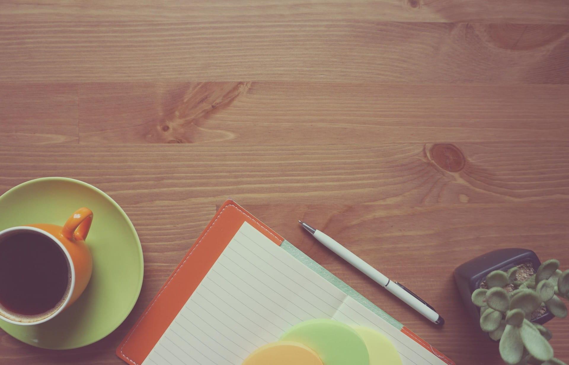 Holzfläche, auf der eine Kaffeetasse und ein Notizblock stehen
